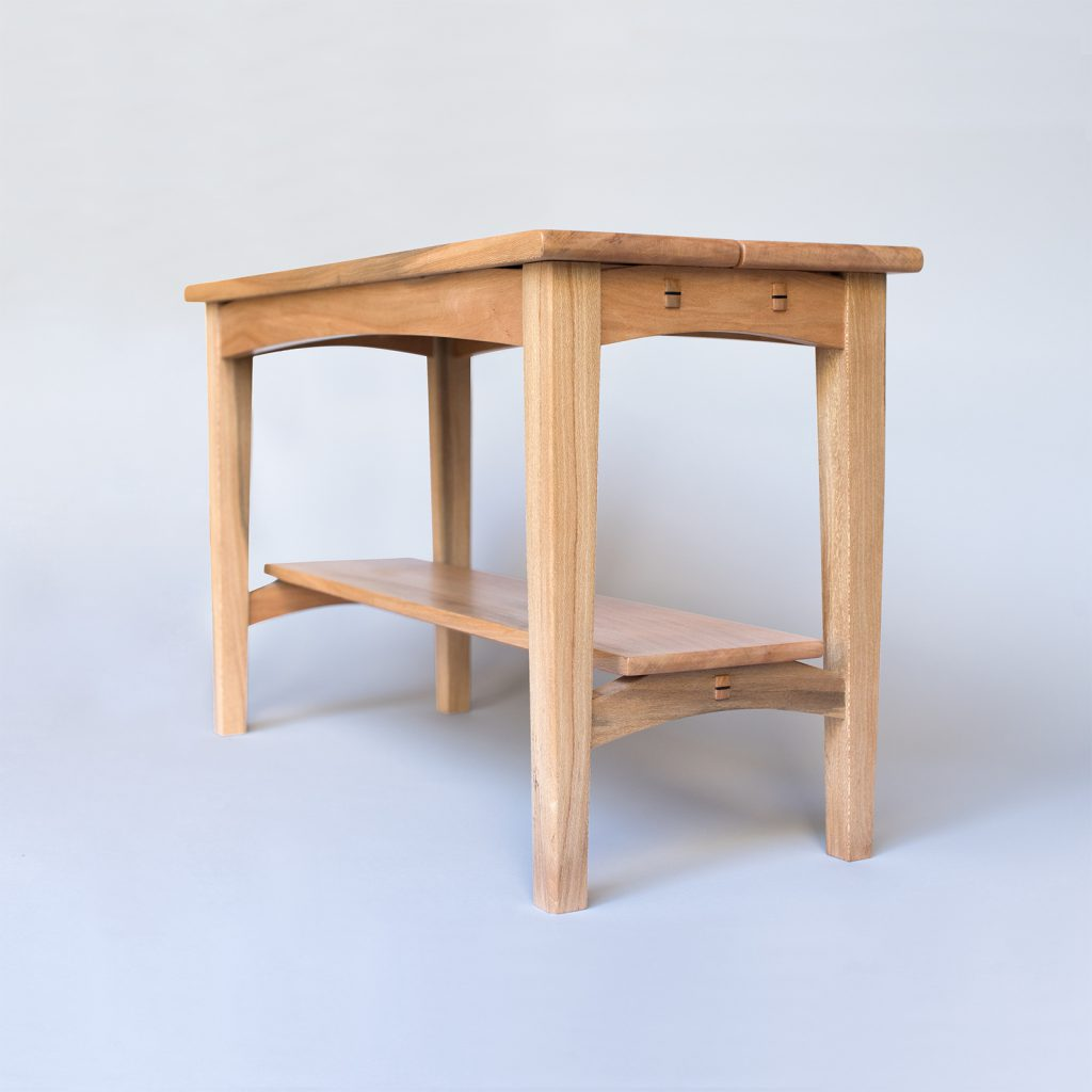 Bench with lower shelf, of lighter colored wood.